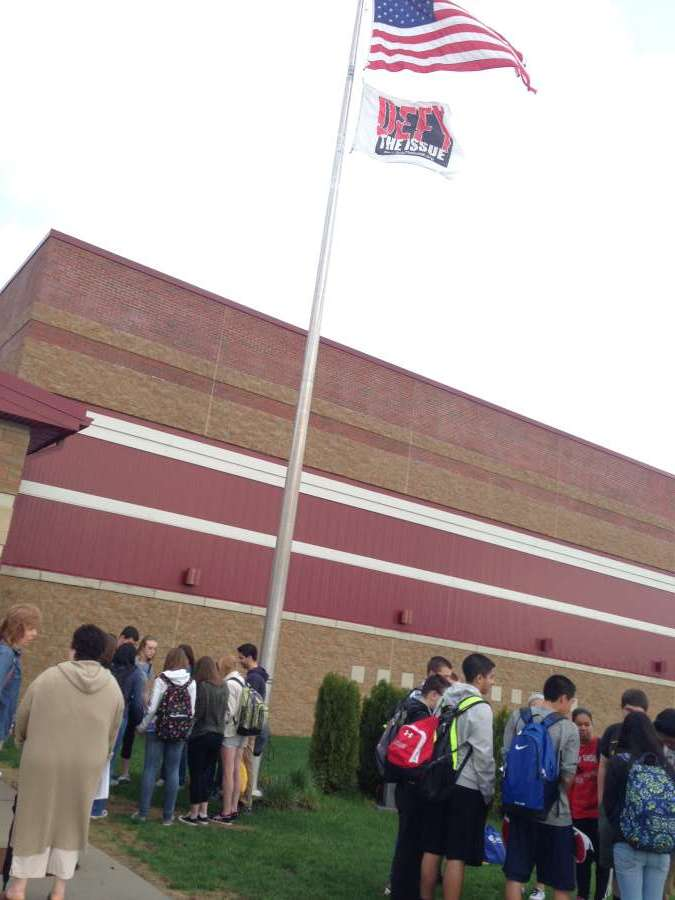 Students stand outside the flag pole.