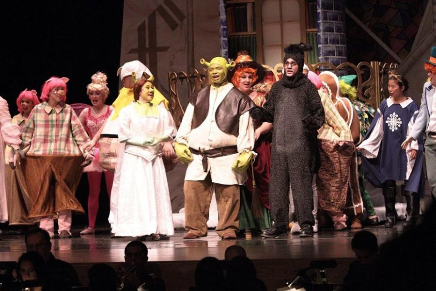 Princess Fiona (Taylor Sternberg), Shrek (Cries Cryer), and Donkey (Will Davis) sing happily with fairy tale creatures