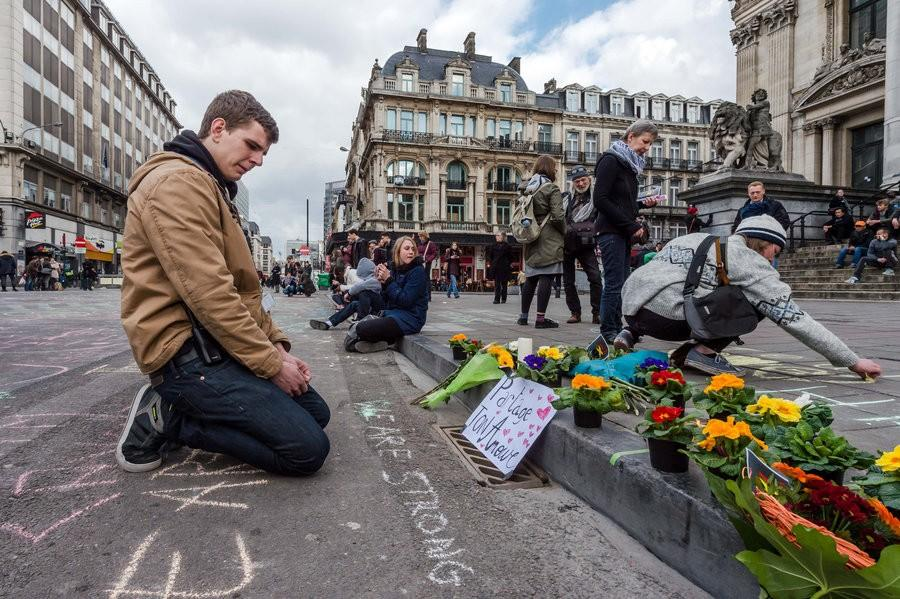 A man looks at flowers and messages of support outside the stock exchange in Brussels (www.npr.org)
