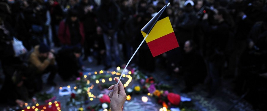 A local holds a paper national flag of Belgium at Beursplein square in honor of those who lost their lives (abcnews.go.com)